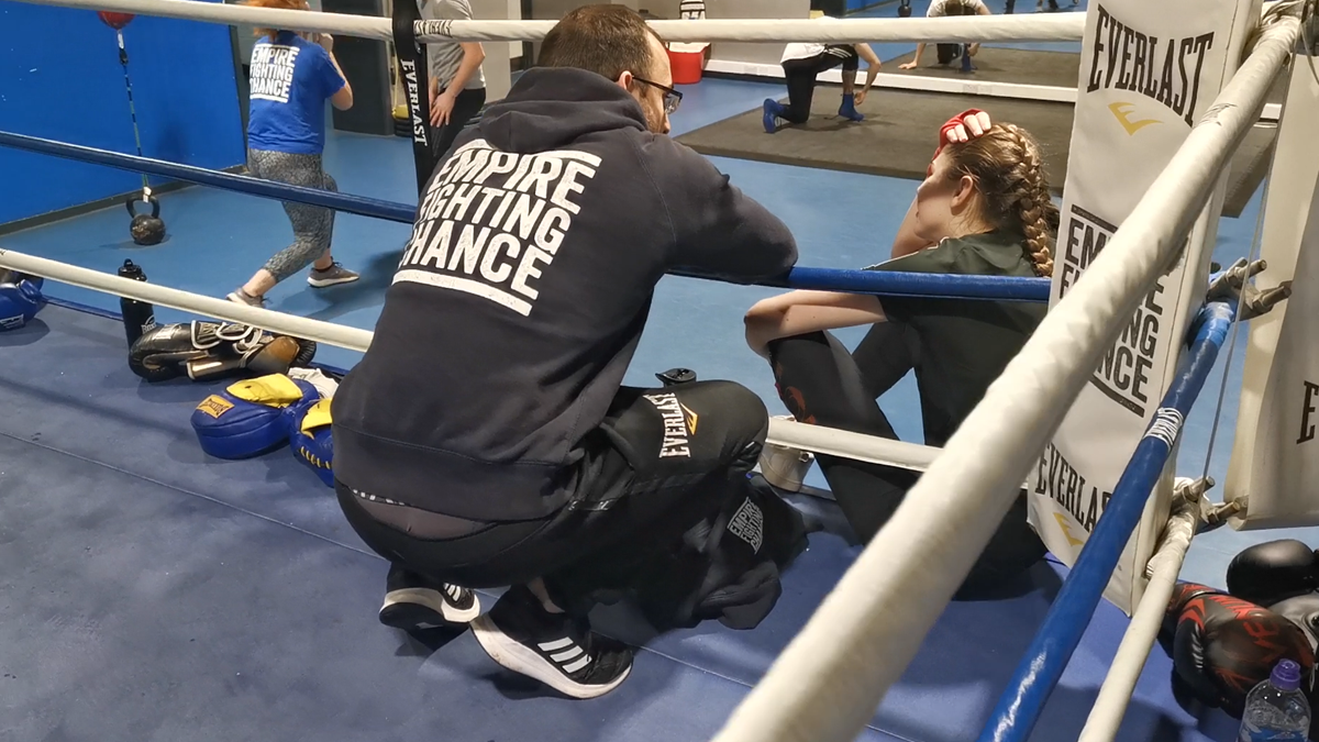 Empire Fighting Chance coach with young boxing mentor in the ring