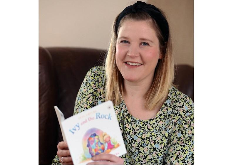 Author Jess Childs holding a copy of Ivy and the Rock