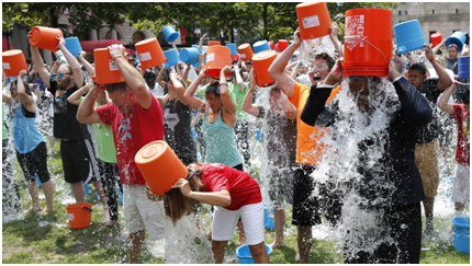 A crowd throwing buckets of ice water over their heads