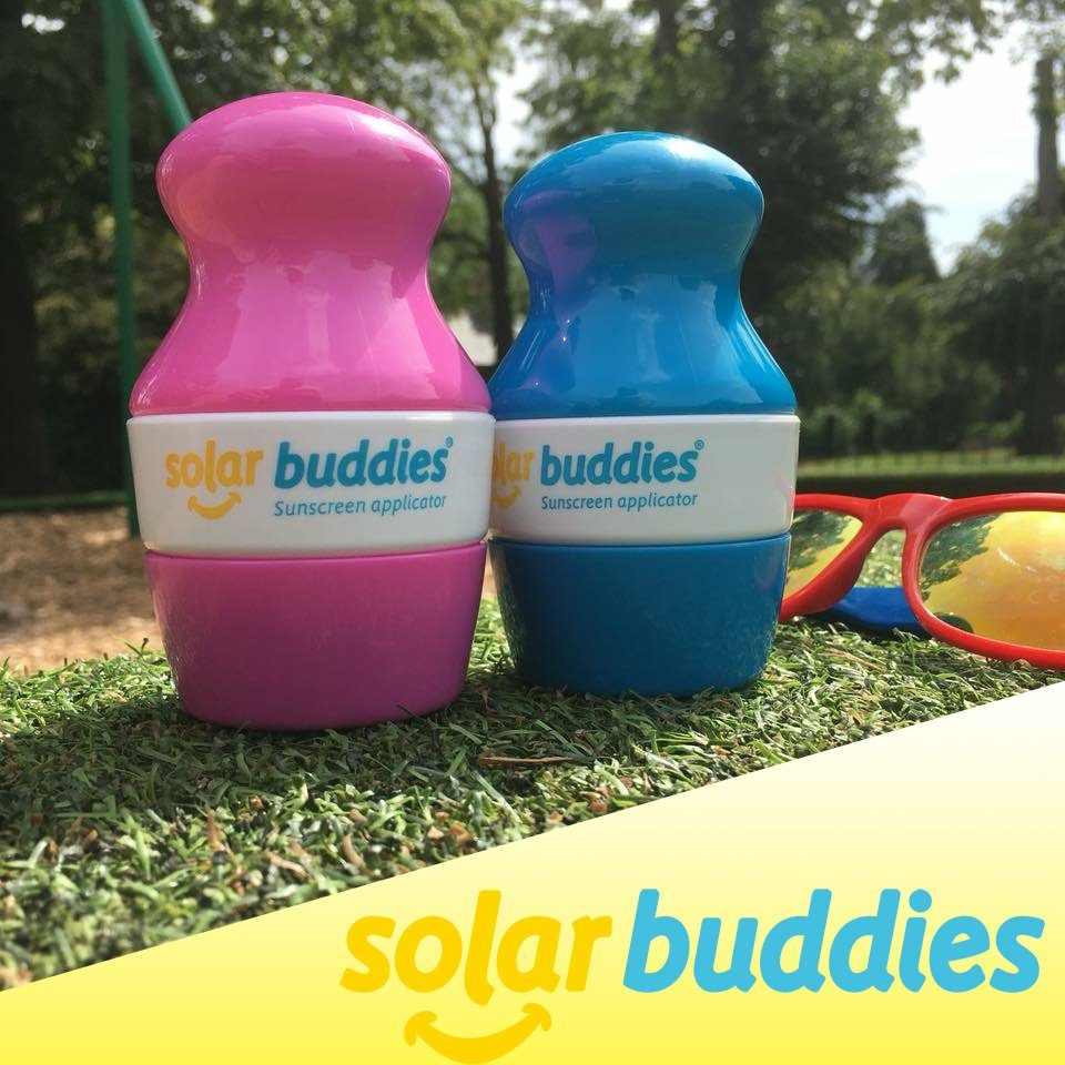 Pink and blue Solar Buddies sitting on the grass