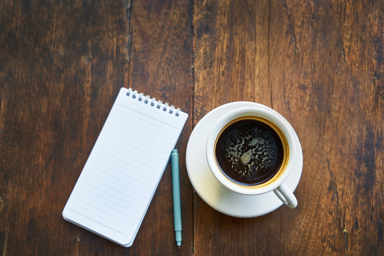 A cup of black coffee and a blank lined notepad and pen laid out on a dark wooden desk