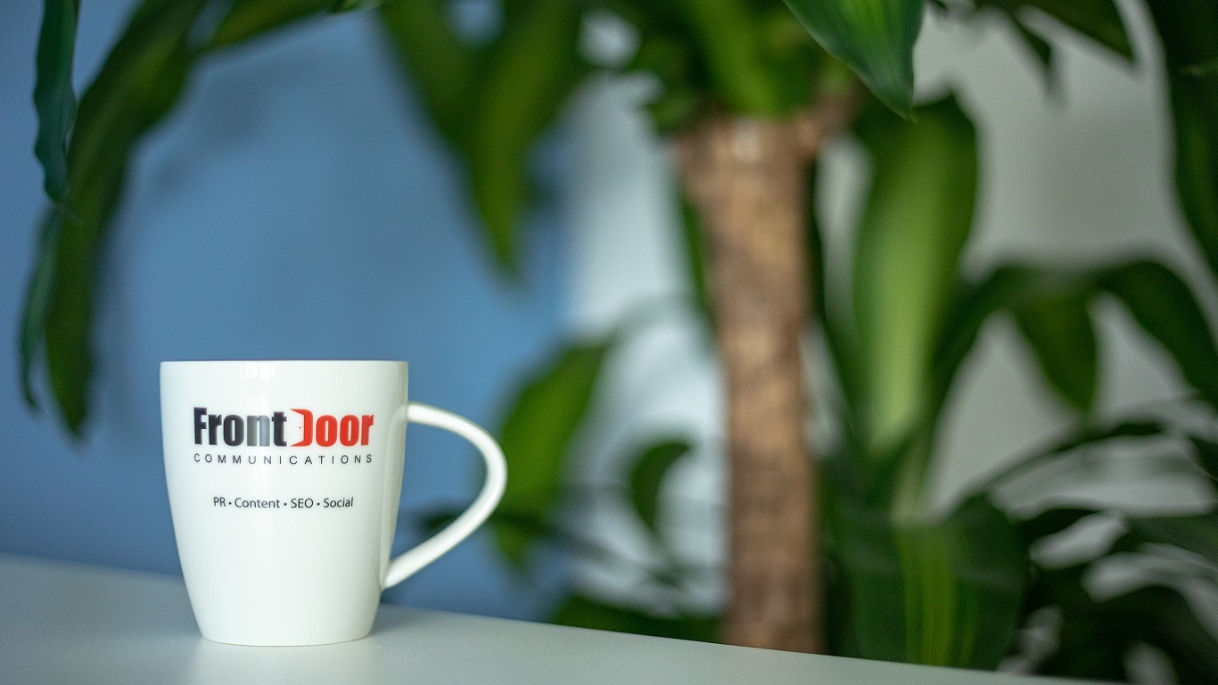 front door comms branded white mug on a desk with a leafy green plant in the background