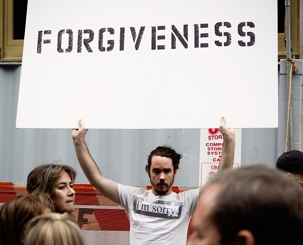 man in white 'I'm sorry' tee shirt holding up a large forgiveness sign