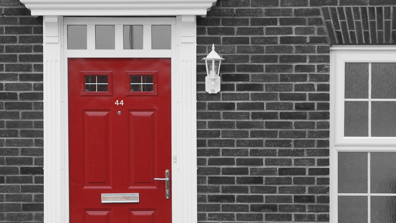 A red front door on a black and white background