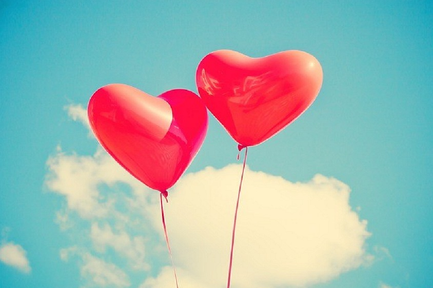 two red love heart balloons floating in a cloudy blue sky
