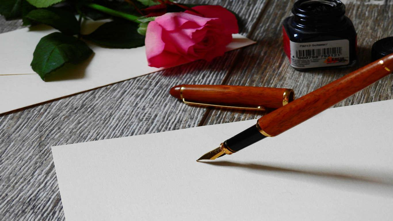 Pen poised to write letter with pink rose in the background