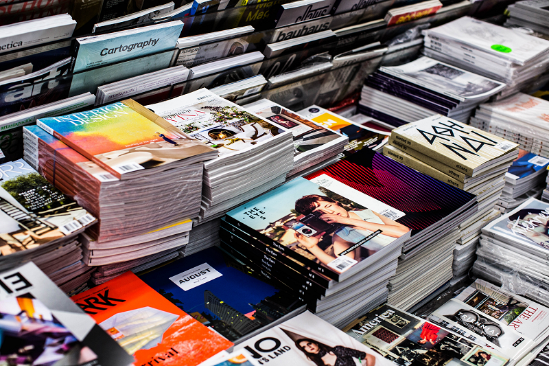 A selection of full colour magazines set out on a table for sale