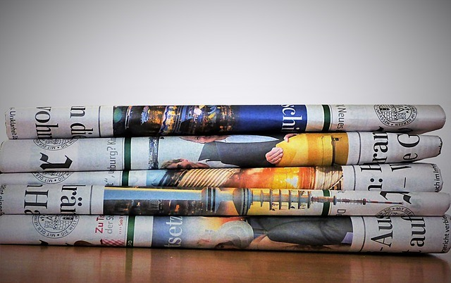A stack of folded newspapers on a wooden desk