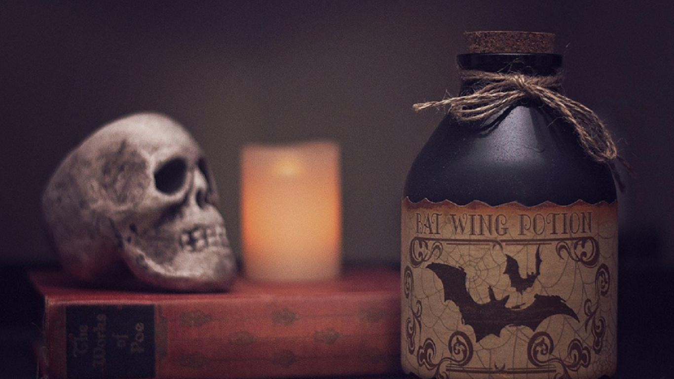 a skull, candle, book and potions bottle on a desk