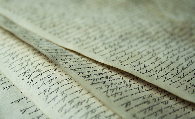 Four sheets of handwritten parchment spread out in a fan