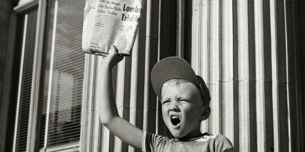 black and white photo of an olden days paperboy shouting out headlines