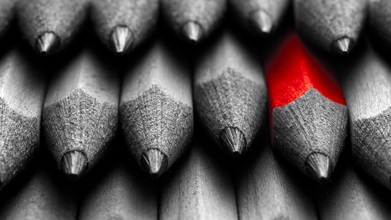 one red pencil among a pile of black and white pencils