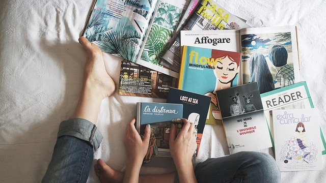 A woman sat on the bed surrounded by magazines.