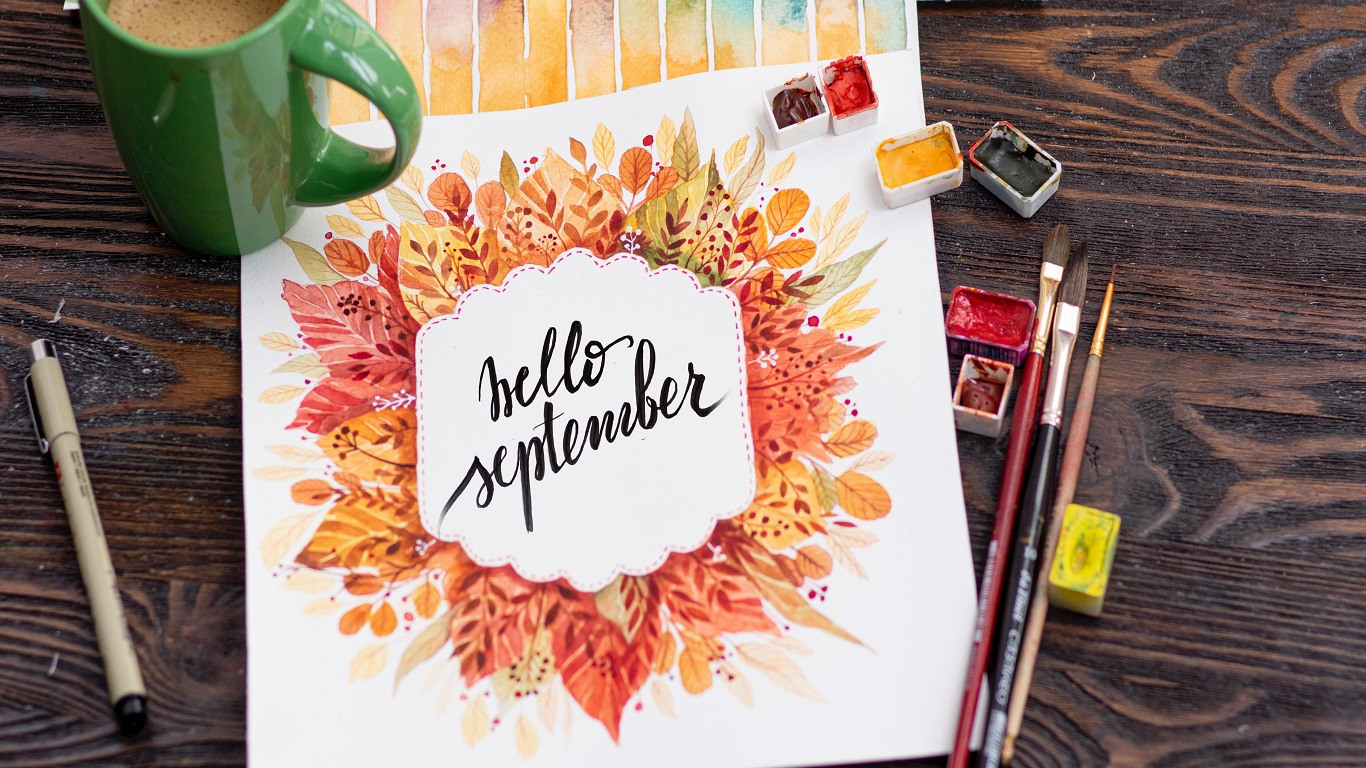 'Hello September' painting on a wooden desk with paints and a mug of tea.