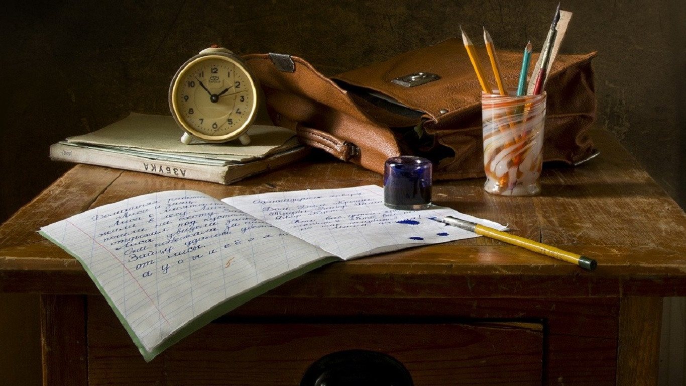 School desk covered with a book, pens, satchel and clock.