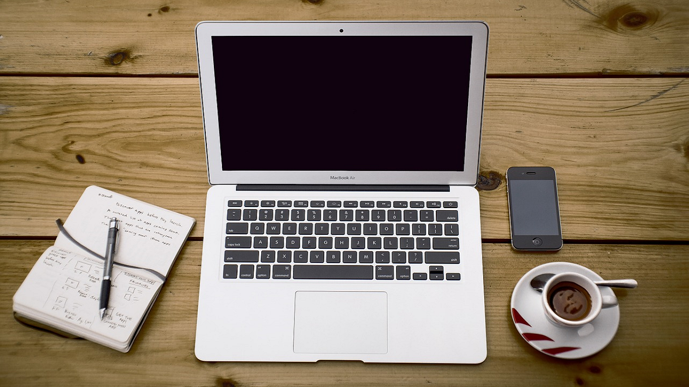 A notepad and pen, open macbook, coffee and a smartphone set out on a wooden desk.